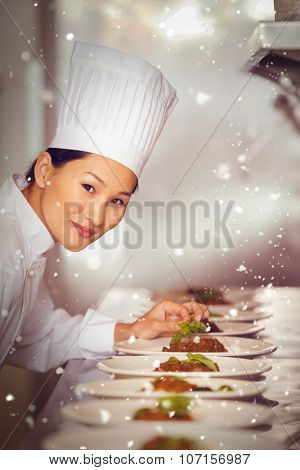 Snow against smiling female chef garnishing food in kitchen
