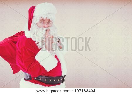 Santa keeping a secret and holding his sack against room with wooden floor