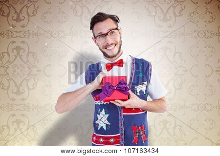 Geeky hipster offering christmas gift against elegant patterned wallpaper in neutral tones