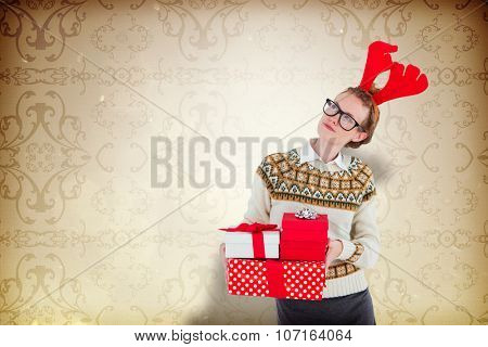 Thoughtful geeky hipster holding presents against elegant patterned wallpaper in neutral tones