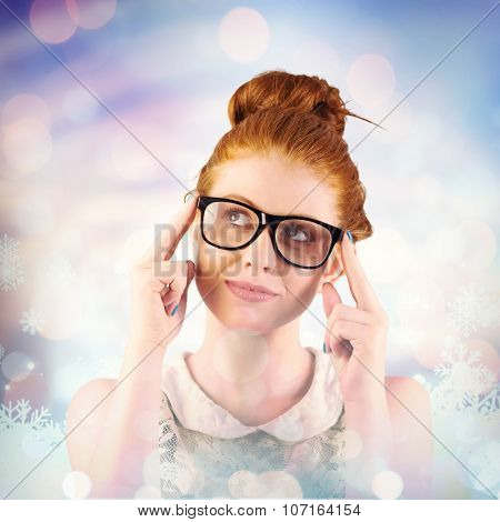 Hipster redhead looking up thinking against snowflake pattern