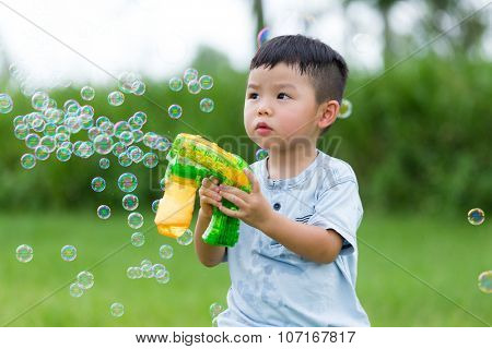 Little boy play with the bubble gun machine