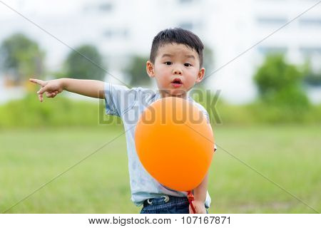 Little boy hold with balloon and finger point aside