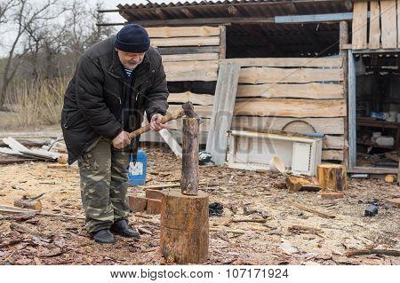 Old Ukrainian peasant choping firewood