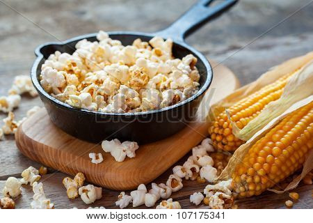 Prepared Popcorn In Frying Pan On Cutting Board, Corn Seeds In Bowl And Corncobs On Kitchen Table.