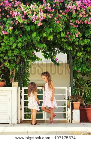 Two cute little girls talking and playing near the house