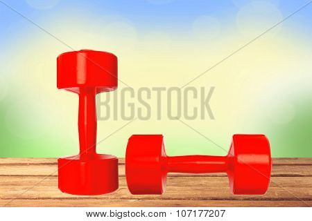 Red Dumbbells Fitness On Wooden Table Over Nature Background