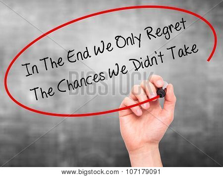Man Hand writing In The End We Only Regret The Chances We Didn't Take with black marker on visual sc