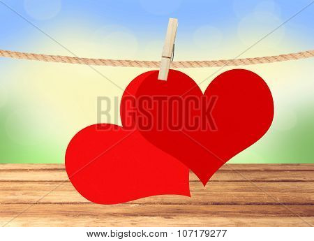 Two Red Hearts Hang On Clothespin Over Blurred Nature Background