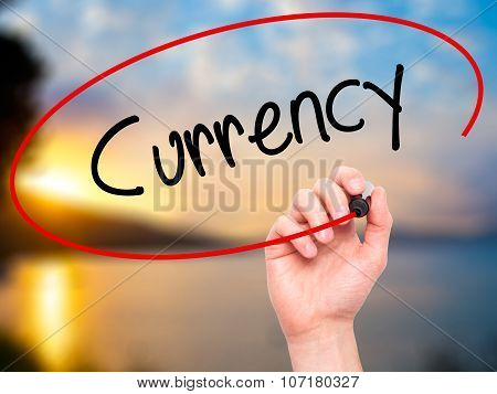 Man Hand writing Currency with black marker on visual screen.