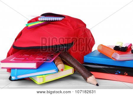 Red bag with school equipment on wooden table isolated on white