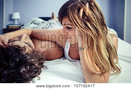 Young woman caressing man face lying over bed