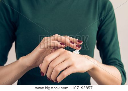 Woman In A Green T-shirt And A Maroon Manicure Applying Hand Cream