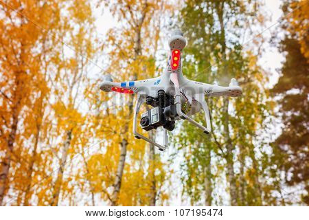 STRASZYN, POLAND - OCTOBER 20 ,2015: Flying drone quadcopter Dji Phantom 2 with digital camera GoPro HERO4 in autumnal scenery.