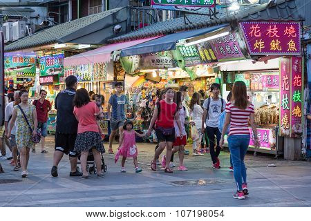 Shoppers Walking Past Stores At Danshui Riverside Shopping Area