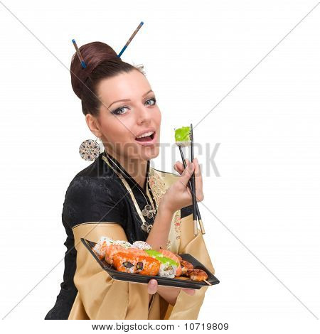 Young Woman Wearing A Traditional Dress Eating Sushi, Isolated On White