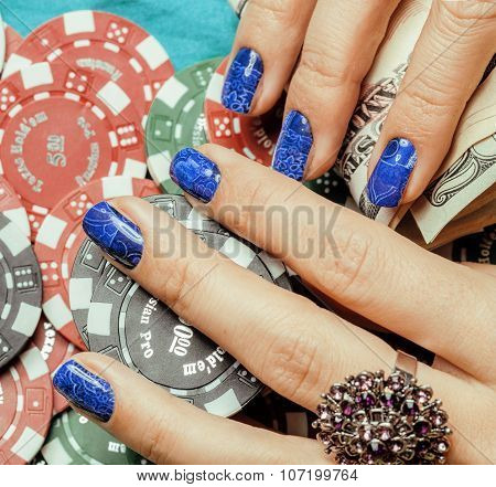 hands of young caucasian woman with blue manicure at casino table close up, deep indigo design on na