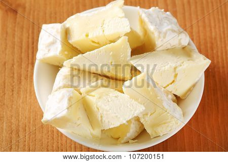 close up of sliced soft white rind cheese in white bowl
