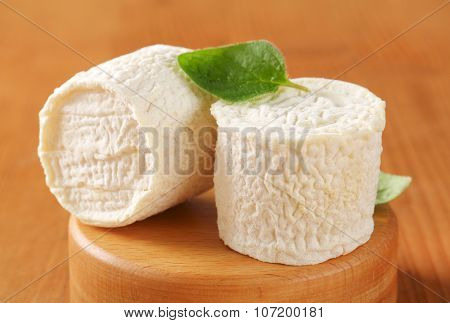 close up of two soft white rind cheeses on wooden cutting board
