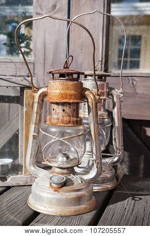 Rusted Kerosene Lamps Stands On Wooden Table