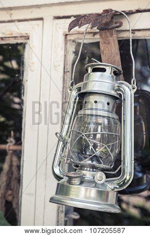 Shining Metal Kerosene Lamp Hangs On White Frame