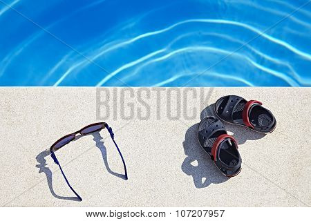 Sunglasses And Sandals At The Swimming Pool