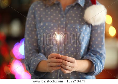Female holding beautiful sparkler on Christmas background at home