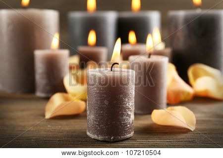 Alight wax grey candle with flower petals on wooden background