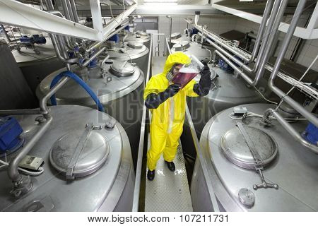 professional with sample in container, in protective uniform,mask,goggle s,gloves and wellies controlling industrial process