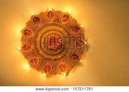 Top view of an illuminated terra-cotta Diwali lamp. View from above.