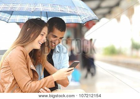 Interracial Couple Sharing A Phone In A Train Station
