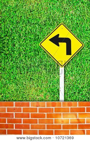 Turn Right Traffic Sign On Brick Wall And Grass Field