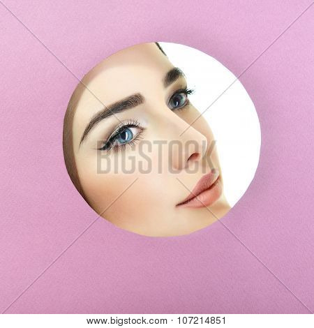 Beauty female portrait. Young beautiful woman look out of circle in purple paper. Girl's face in round paper frame with copyspace for your message