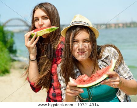 Happy girls eating watermelon on the beach. Youth lifestyle. Happiness, joy, friendship, holiday, beach, summer concept. Young people having fun outdoor.