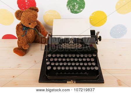 vintage bear and old black typewriter with blank paper