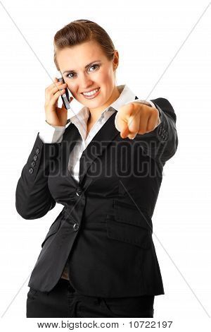 Smiling modern business woman talking on mobile phone and pointing finger at you