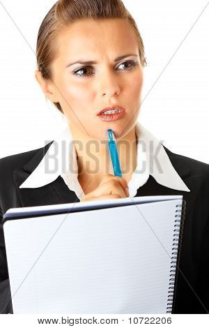 Thoughtful modern business woman holding notebook and pen