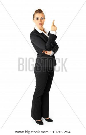 Full length portrait of interested modern business woman pointing finger up