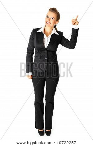 Full length portrait of smiling modern business woman pointing finger in corner