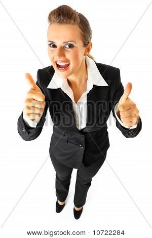 Full length portrait of pleased modern business woman showing thumbs up gesture