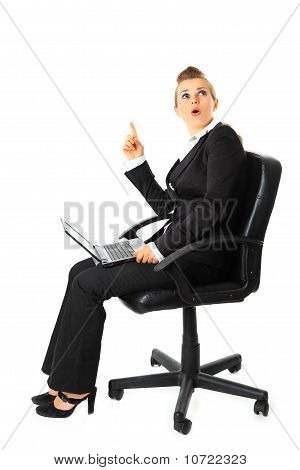 Sitting on chair with laptop surprised modern business woman got idea