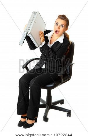 Shocked modern business woman searching something in briefcase