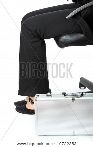 Suitcase at legs of business woman sitting on chair