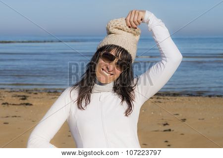 Middle-aged woman playing with her woollen cap at the beach