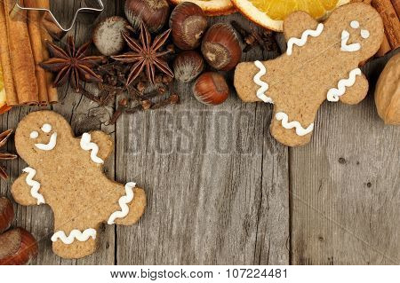 Christmas baking ingredients with gingerbread men over rustic wood