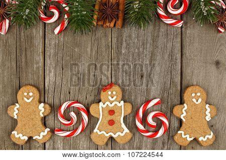 Christmas gingerbread cookies, peppermints and decor on rustic wood