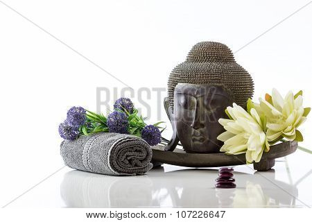 Buddha head on a white background, towel, stones and lotus