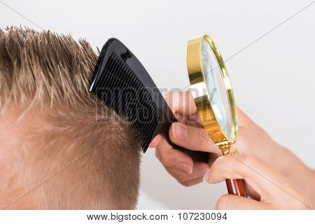 Doctor Looking At Patient's Hair Through Magnifying Glass