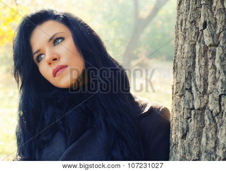 Portrait Of Beautiful Sad Girl In Forest On Sunny Autumn  Day