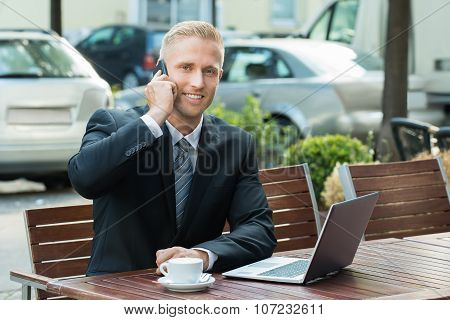 Businessman Talking On Cellphone Looking At Laptop